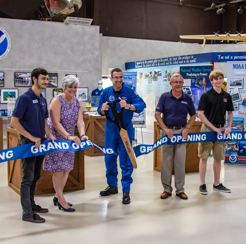 Group of people cutting ribbon in front of NOAA exhibit at Florida Air Museum