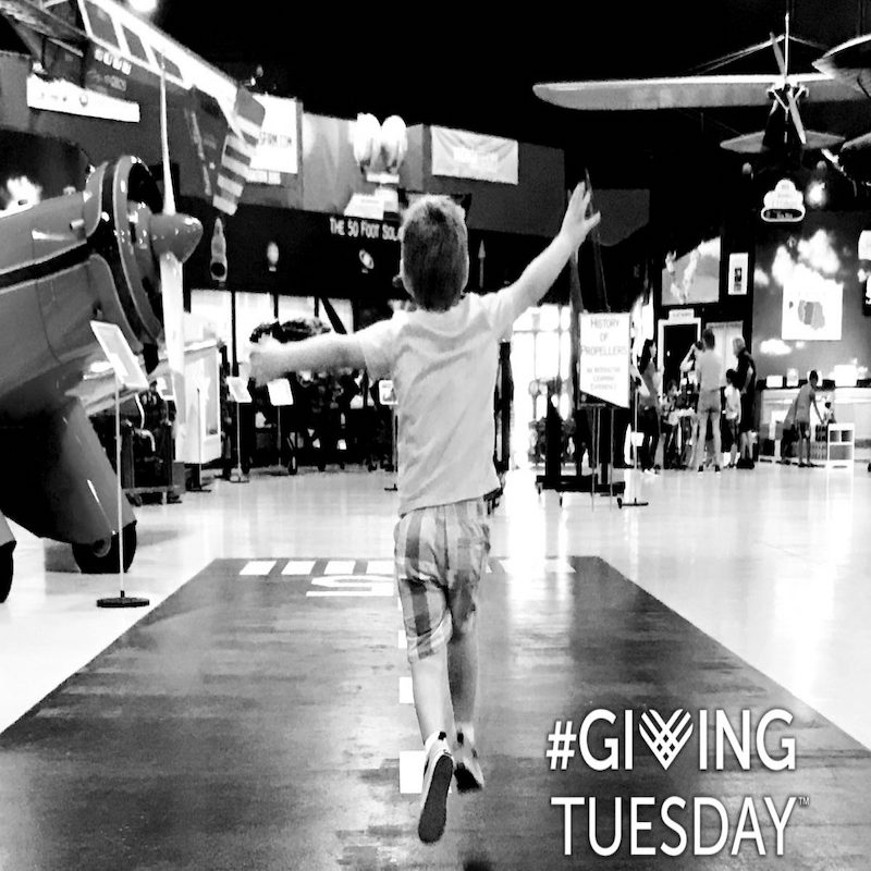 Young man enjoying a run down the runway between the exhibits at Florida Air Museum in support of Giving Tuesday