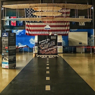 Biplane over runway exhibit with US flag behind - Florida Air Museum main floor