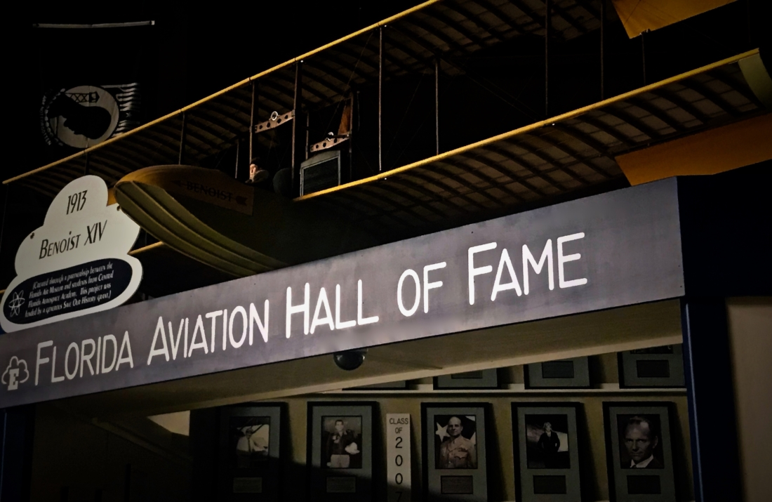 """Black sign entitled """"Florida Aviation Hall of Fame"""" hangs underneath a 1913 Benoist XIV aircraft and over the photos of the Aviation Hall of Fame inductees at the Florida Air Museum in Lakeland, Florida"""