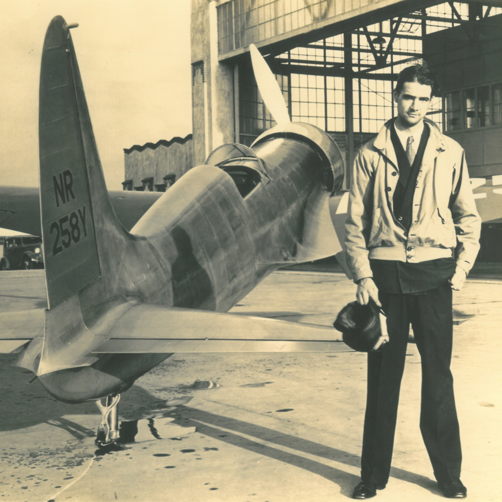 Howard Hughes stands beside a large hangar and his one-of-a-kind Hughes H-1 Racer
